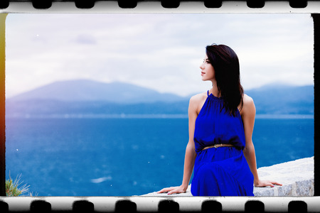 photo of the beautiful young woman sitting on the stone railing and looking at the splendid view in Greece . Image made with old film frame.