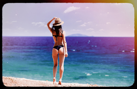 photo of the beautiful young woman standing on the beach resting in Greece . Image made with old film frame.