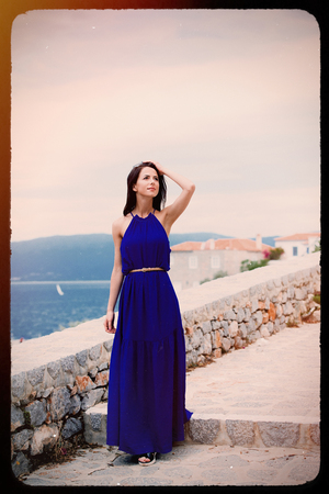 portrait of the beautiful young woman walking on the stone stairs of Greece . Image made with old film frame. Imagens