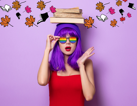 Portrait of young style hipster girl with purple hair and booksand leaves on purple color background 스톡 콘텐츠
