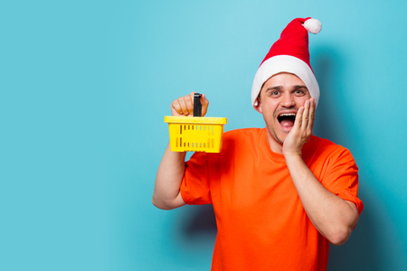Young handsome man in orange t-shirt with Christmas hat and supermarket basket. Studio image on blue background