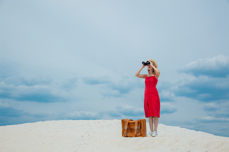 Young woman in red dress with suitcase looking in binoculars on the beach. Travel concept image on sand Stok Fotoğraf