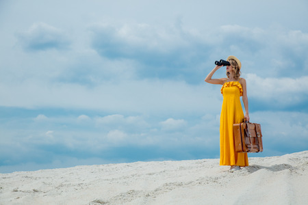 Young woman in yellow dress with suitcase looking in binoculars on the beach. Travel concept image on sand