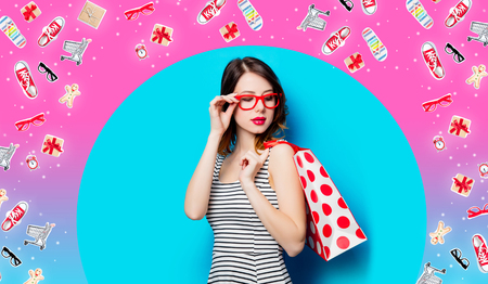 portrait of beautiful young woman with shopping bag on the wonderful blue studio background and with clothes Stock Photo