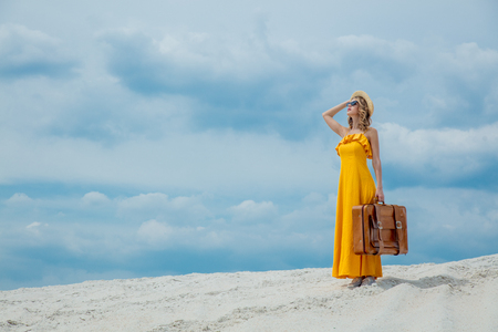 Young woman in yellow dress with suitcase on the beach. Travel concept image on sand
