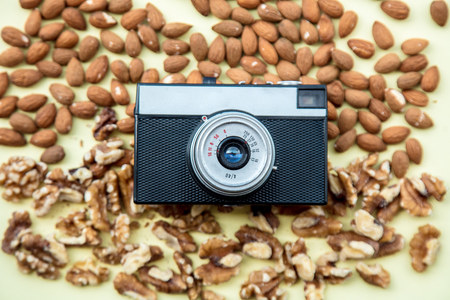 Almonds and walnuts with vintage camera on green background. Above view