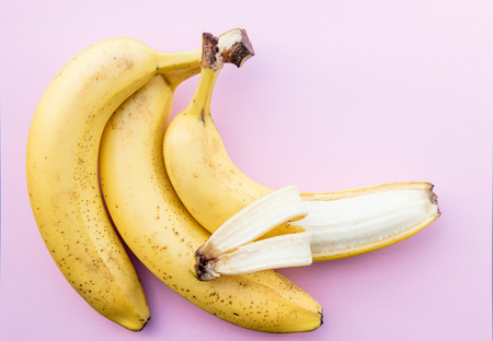 Yellow bananas on clear pink background. Above view