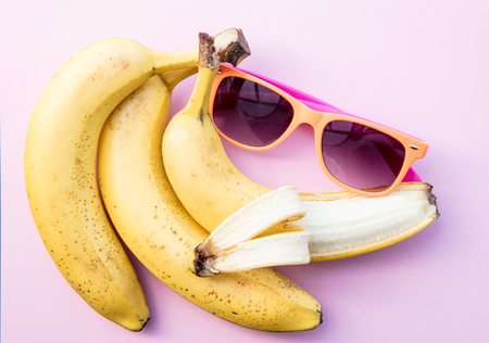 Yellow bananas and sunglasses on clear pink background. Above view Stock Photo