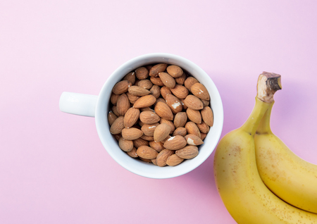 White cup full of almonds with banana on pink background. Above view