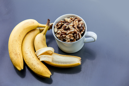 White cup full of Walnuts with banana on grey background. Above view