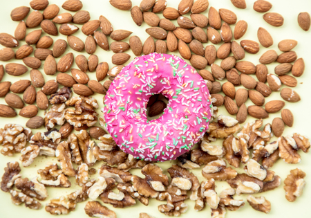 Almonds and walnuts with pink donut on green background. Above view