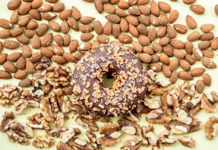 Almonds and walnuts with chocolate donut on green background. Above view Stock Photo
