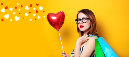 Young red-haired woman with heart shape toy and shopping bags on yellow background