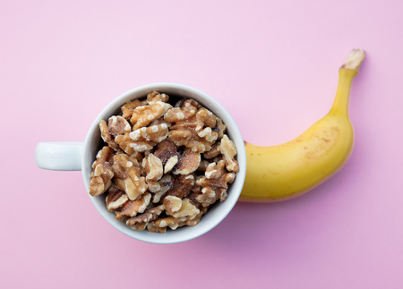 Half of banana and cup with walnuts on pink background. Above view Stock Photo