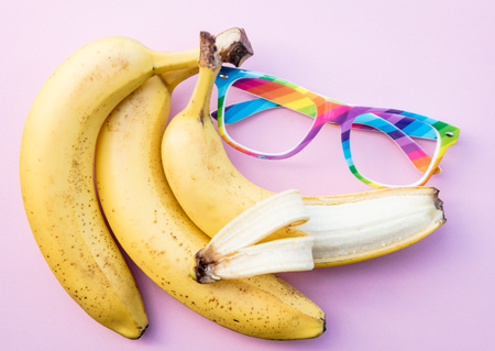 Yellow bananas and LGBT colors glasses on clear pink background. Above view