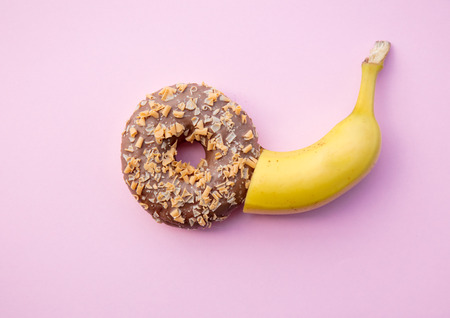 Fresh sweet donut and banana on pink background. Abive view Stock Photo