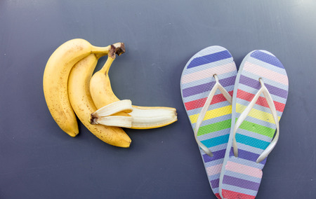 Summer sandals with banana on grey background. Above view Stock Photo