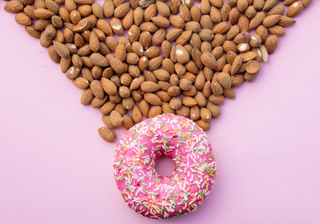 A lot of almonds and sweet donut on pink background. Above view