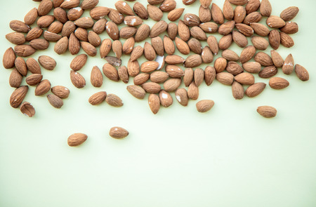 Almonds isolated on green background. Above view