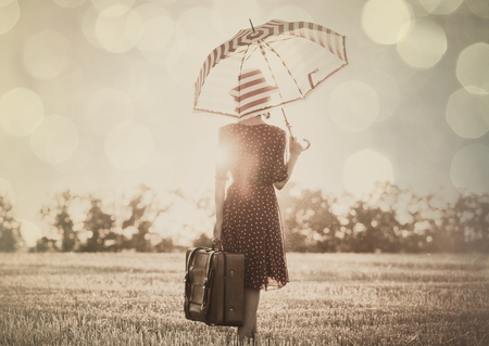 photo of the beautiful young woman with red umbrella and brown suitcase standing in the field Stock Photo