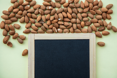 Almonds and blackboard on green background. Above view