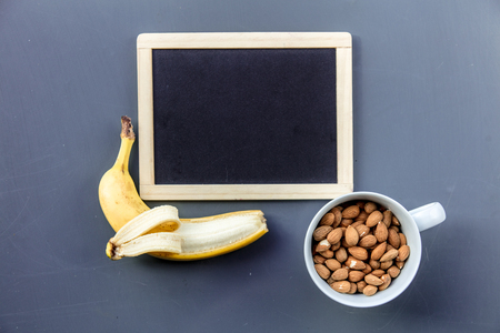 White cup full of almond with banana near blackboard on grey background. Above view Stock Photo