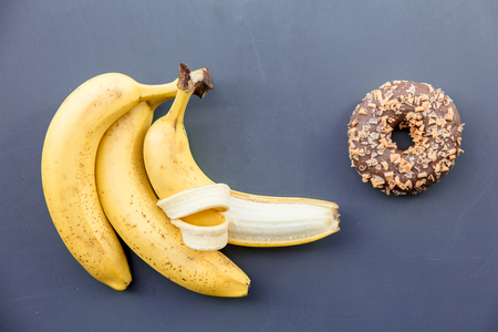 Sweet donut with banana on grey background. Above view