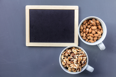 White cups full of almonds and walnuts near blackboard on grey background. Above view Stock Photo