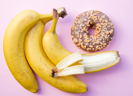yellow banana and donut on pink background. Above view Stock Photo