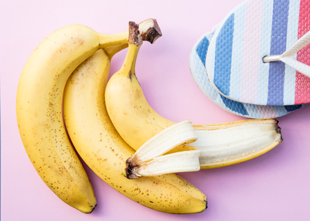 Yellow bananas and summer flip flops on clear pink background. Above view