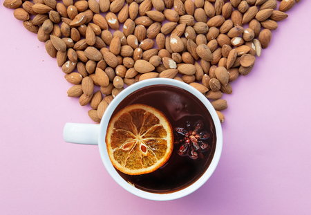 A lot of almonds and cup of tea on pink background. Above view Stock Photo