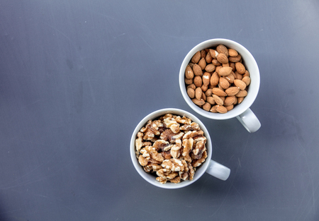 White cups full of almonds and walnuts on grey background. Above view