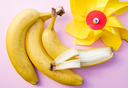 yellow banana and pinwheel on clear pink background. Above view