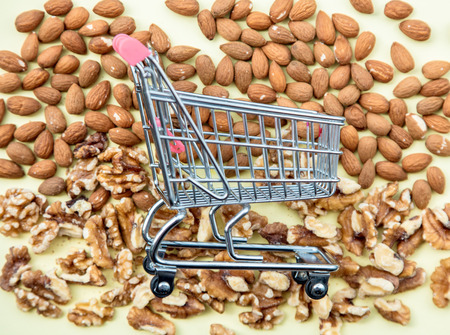 Almonds and walnuts with supermarket cart on green background. Above view