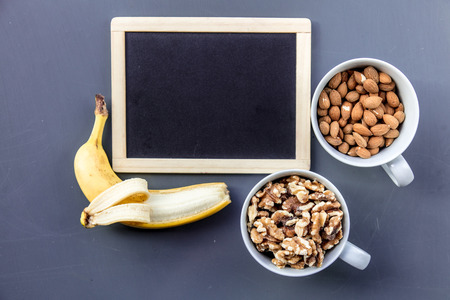 White cups full of almonds and walnuts with banana near blackboard on grey background. Above view