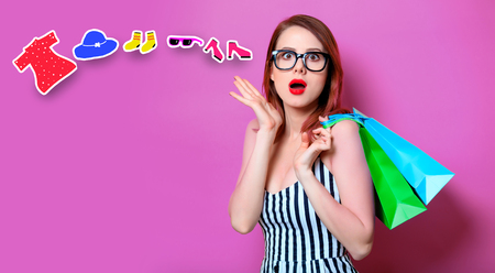 Red-haired woman in black glasses with colour shopping bags on yellow background Stock Photo