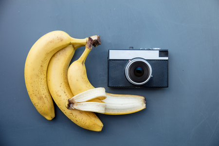 Vintage camera with banana on grey background. Above view Stock Photo