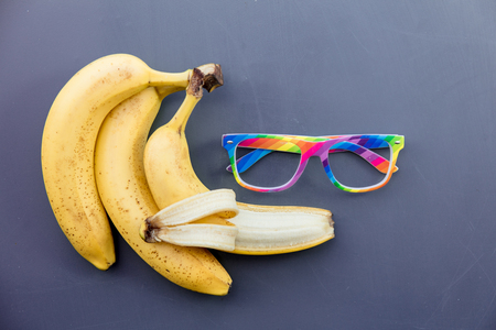 Colored glasses with banana on grey background. Above view