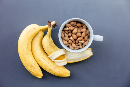 White cup full of almonds with banana on grey background. Above view
