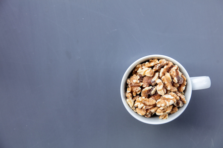 White cup full of walnuts on grey background. Above view