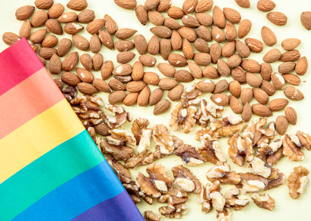 Almonds and walnuts with LGBT flag on green background. Above view Stock Photo