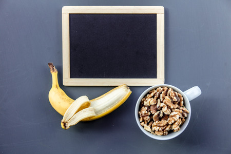 White cup full of Walnuts with banana near blackboard on grey background. Above view