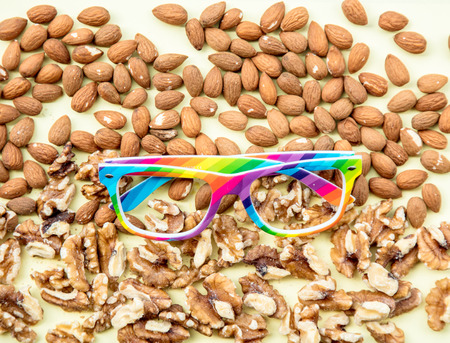 Almonds and walnuts with LGBT colors glasses on green background. Above view Stock Photo