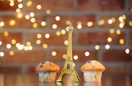 Homemade classic cupcakes and Eiffel tower souvenir. Fairy lights and gift box in bokeh background. Christmas time concept