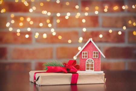 Christmas gift box and wooden toy house on background with fairy lights in bokeh. Holiday season Stock Photo