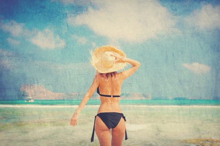 Young redhead girl in black bikini and with hat on Balos beach, west Crete, Greece. Summertime season vacation, July. Image in retro style Stock Photo