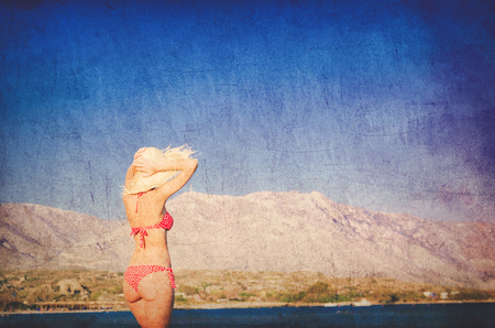Young redhead girl in hat and bikini on Elafonissi beach, west Crete, Greece. Summertime season. Image in retro style Imagens