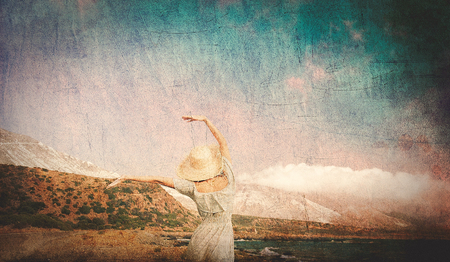 Caucasian girl in hat and white dress on sea coast in summertime. Stomio region, west Crete, Greece. Image in retro style