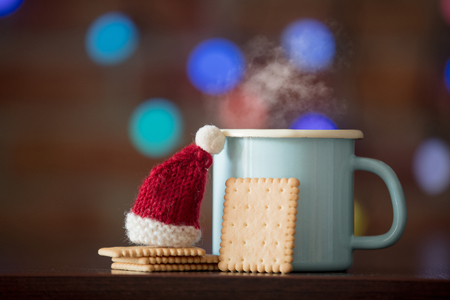 Hot cup of coffee and classic cookie, Santa Claus hat with fairy lights on background. Christmas season