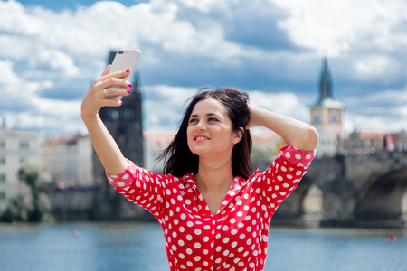 Beautiful brunette girl in red dress make a selfie in Prague, city streets